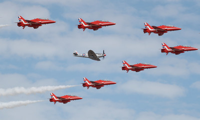 The Red Arrows, Royal Air Force Aerobatic Team, are joined by a Spitfire at the opening of the Farnborough Airshow, in Farnborough