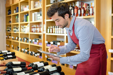 winemaker in cellar controlling wine market prices on tablet