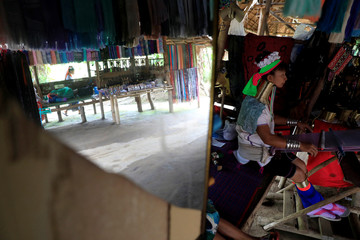 An Ethnic Kayan also know as a Long Neck woman weaves in her souvenir shop in the Kayan village at the northern province of Chiang Rai