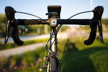 Front view of a road bike with cycling computer and sport action camera on the handlebar stem during sunset