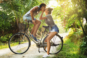 Young couple is riding a vintage bicycle on the country road in tropical country