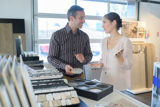 happy couple choosing for buying wallpaper looking at design