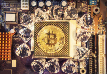 A golden physical bitcoin (digital virtual crypto-currency) placed over the CPU socket of a motherboard, surrounded by shiny diamonds.