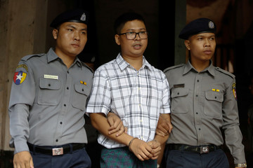 Detained Reuters journalist Wa Lone is escorted by police officers at Insein court in Yangon