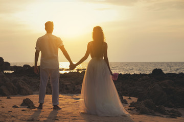Wedding on the beach - Young married couple holding hands