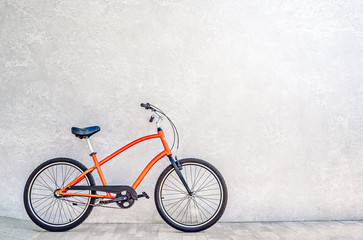 Orange color city bike against the wall with shiny silvery metallic plaster. Summertime concept Wall mural