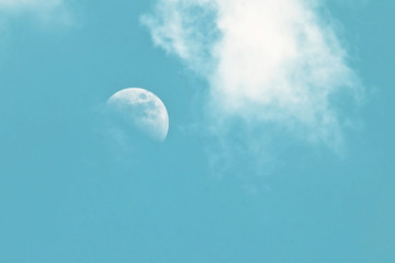 Pale morning moon in a blue sky with clouds as a background