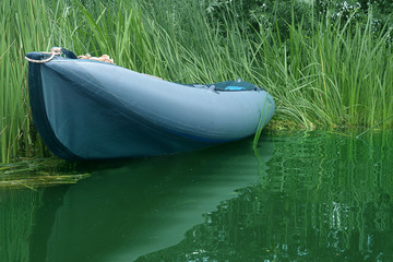 Inflatable bomarka is approached by a river overgrown with tall grass