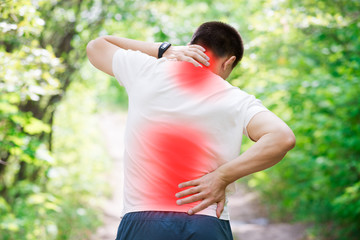 Man with back pain, injury while running, trauma during workout