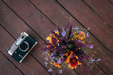 Vintage retro camera and spring flowers branches on rustic wooden table. top view. flatlay