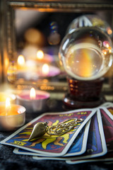 Tarot cards, crystal orb, pendulum, candellight  and a mirror, magic night scene