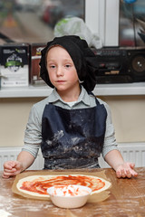 Pizza, children and the concept of cooking - children make pizza. Preparation of pizza, a master class for children and a fuzzy focus on ingredients for pizza.