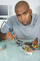 Portrait of man using soldering iron