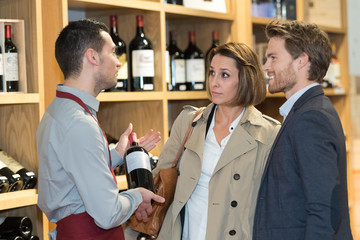 salesman offering bottle of red wine to young couple