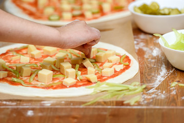 Close-up of children's hands preparing pizza. Children lay out on the basis of pizza vegetables and cheese