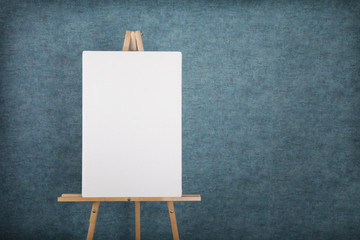 Wooden easel with blank canvas against a blue wall Wall mural