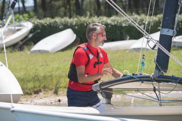 portrait of mature sportsman near catamaran