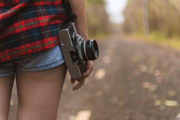 Enjoyment - free happy woman enjoying beautiful woman with vintage camera wearing shorts on the road with vintage filter effect