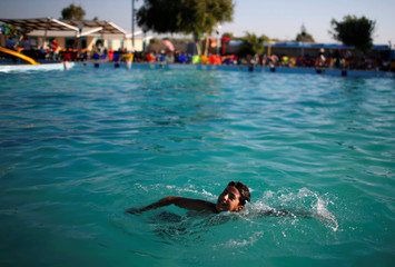 Palestinian boy swims at Sharm Park Water City, in Gaza