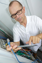 men with tablet in data storage service room close up