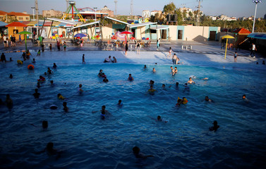 Palestinians swim at Sharm Park Water City, in Gaza