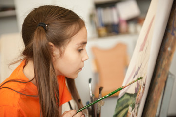 Portrait of a lovely little girl painting a picture in a studio or art school. Creative pensive painter child paints a colorful picture on canvas in workshop. Talented kids