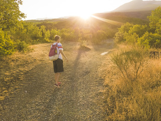 young man with backpack walking on a mountain road tourist nature concept