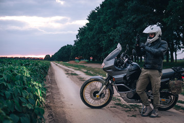Biker Man in leather jacket standing outdoor with his Adventure Motorcycle, off road travel concept, enduro rider equipment, extreme lifestyle, copy space