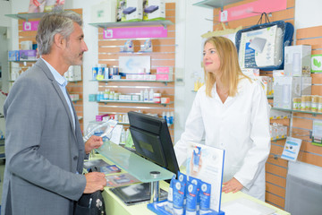 Man being served in pharmacy
