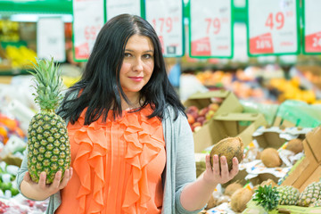 Shopping concept. Smiling woman with pineapple and coconut in the supermarket store.