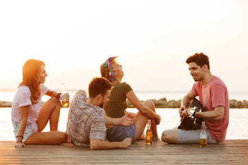 Happy friends sitting outdoors on the beach play on the guitar drinking beer.