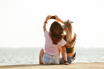 Women sitting outdoors on the beach take a selfie.