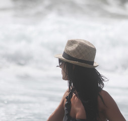 Beautiful girl with hat at the sea who walking in the water. The sea in the background. Sabaudia, Lazio, Italy
