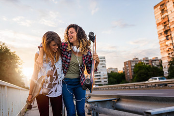 Smiling skate girls holding long-boards walking outdoors in the street having fun