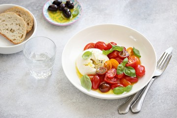 Mozzarella and cherry tomatoes salad with fresh basil and olives.