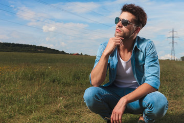 young casual man crouching in a field and thinking