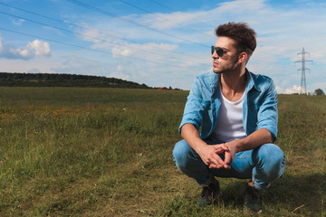 casual man with sunglasses squatting and looking to side