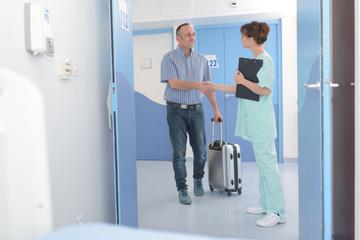smiling nurse welcoming patient in hopsital