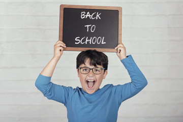 back to school, happy child with a blackboard on brick background