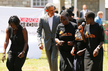 Former U.S. President Barack Obama joins traditional dancers as he tours the Sauti Kuu resource centre near his ancestral home in Nyangoma Kogelo village in Siaya county