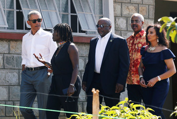 Former U.S. President Barack Obama listens to Auma Obama as he tours the Sauti Kuu resource centre near his ancestral home in Nyangoma Kogelo village in Siaya county