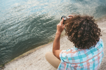 Top view of young male with curly hair checking photos of nature on his digital camera. Young handsome man wears casual shirt, with digital camera posing next to the lake. People, travel, lifestyle