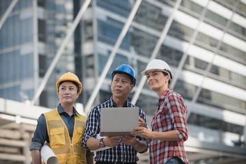 Asian engineers group consult construction on site building working while holding laptop computer and  blueprint paper. in city background. Technology ,teamwork concept.