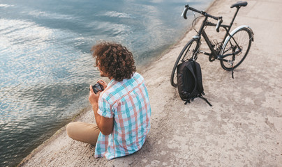 Rear view of young male with curly hair taking photos of nature on his digital camera. Handsome man wears casual shirt relaxing and sitting near to the bike next to the lake. People, travel, lifestyle