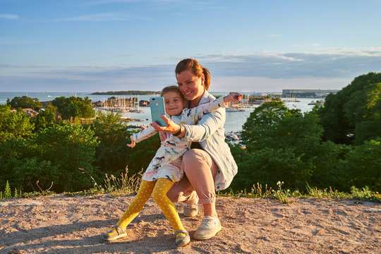Young mother and her daughter taking a selfie, sea on background, Kaivopuisto park, Helsinki, Finland