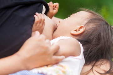 Mother Breast feeding her Baby with Happiness in the Garden