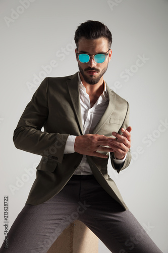 00a082ce011d sexy stylish man wearing sunglasses sits on wooden box