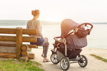 Young sporty mother with stroller sitting on wooden bench near lake or river. Mom walking with baby in pram near pond at early morning. Healthy outdoor sleeping. Toned