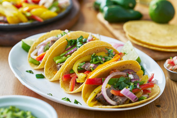 Wall Mural - tacos with beef and bell pepper filling served with guacamole