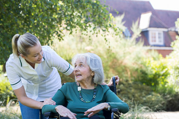 Carer Pushing Senior Woman In Wheelchair In Garden